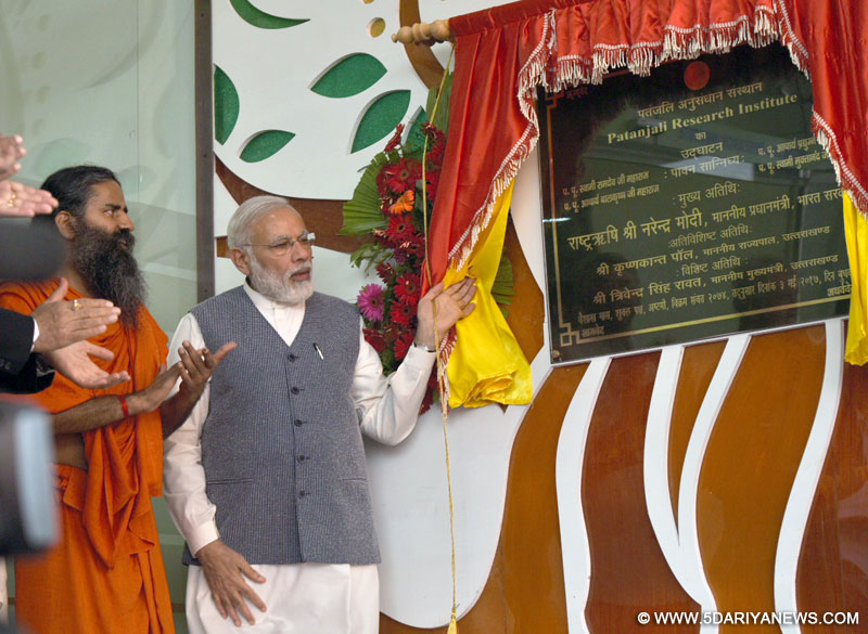 The Prime Minister, Shri Narendra Modi unveiling plaque to mark inauguration of the Patanjali Research Institute, at Haridwar, in Uttarakhand on May 03, 2017. The Guru, Baba Ramdev is also seen.
