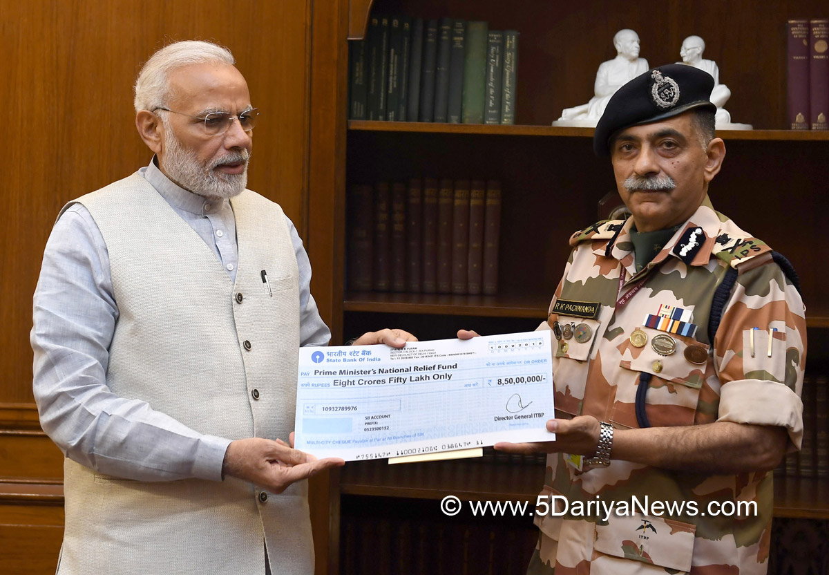 The DG, ITBP, Shri R.K. Pachnanda presenting a cheque of Rs.8.5 crore to the Prime Minister, Shri Narendra Modi, towards the Prime Minister's National Relief Fund, in New Delhi on September 10, 2018. CNR :117947 Photo ID :130520